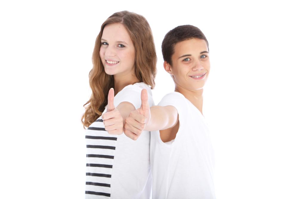 2 teenagers smiling wearing braces